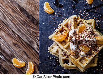 Black board with Viennese waffles, tangerines, chocolate