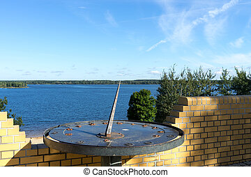 Sundial in front of a Lake with clouds on a sunny day