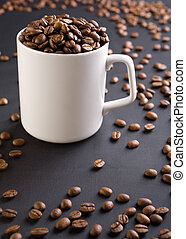 white coffee mug with coffee grains on a black background...
