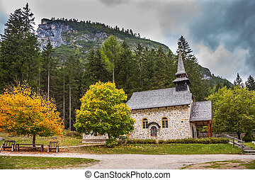 Church on the Alpine lake Lago di Braies. The concept of...