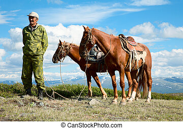 Asian man holding two horses on a background of snow-capped...