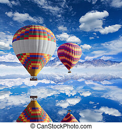 Colorful hot air balloons flies above calm lake