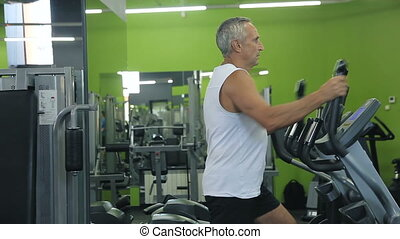 Old man is engaged on simulators in gym. Full HD