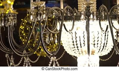 Crystal chandelier with yellow garlands on the dark...