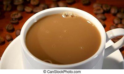 In latte added a lump of sugar and stir, closeup - In latte...