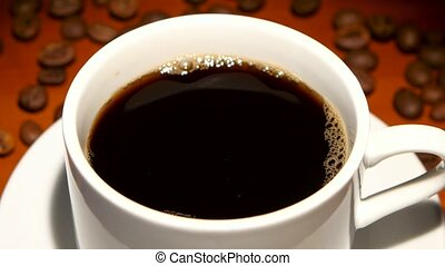 In cup with black coffee falls one piece sugar. Closeup - In...