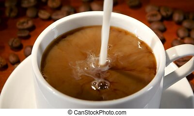 In white cup with hot black coffee added milk. Closeup - In...