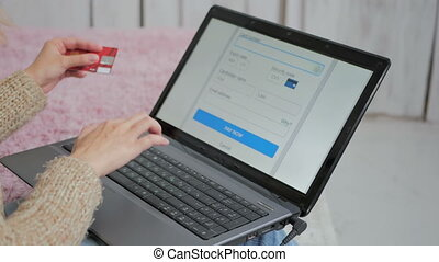 Woman shopping online at laptop with credit card - Young...