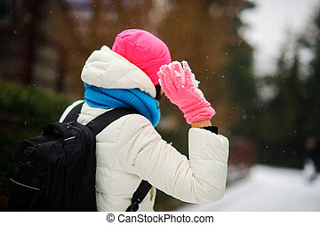Young woman holds a snowball in hand. She is ready to throw...