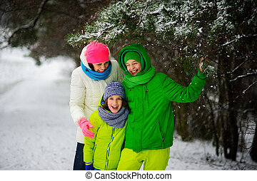 Mother with two sons on walk in winter day.