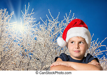 The seven-year-old boy in red Santa Claus's cap - The boy is...