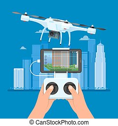 Drone with remote control flying over city. Aerial drone...