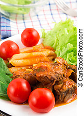 Dish of beef stew with pasta penne and cherry tomatoes -...