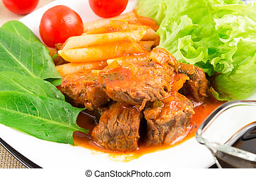 View close-up on a meal of beef stew with penne pasta and...