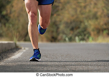 Runner man running on road training for marathon run doing...