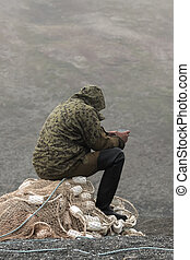 fisherman in camouflage jacket and rubber boots sitting on...