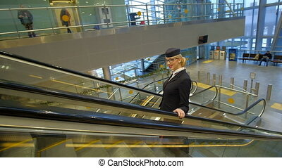 Blonde stewardess rides up on escalator with suitcase at airport