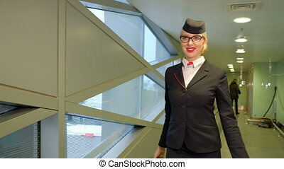 Blonde stewardess walks down hallway at airport terminal indoors