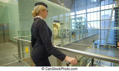 Blonde stewardess standing in waiting room with suitcase in...