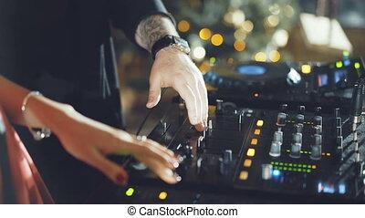 Hands of DJ tweak various track controls on dj's deck in 4K.