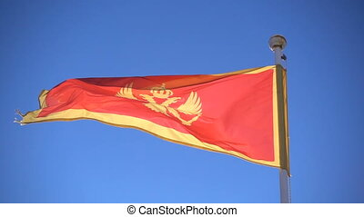 Montenegro flag flying in the background of the sky, slow...