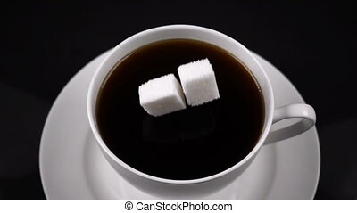 sugar cubes dropped into coffee creating splash, slow motion