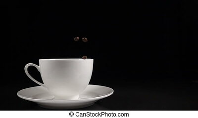 Coffee beans falling into a white cup, slow motion