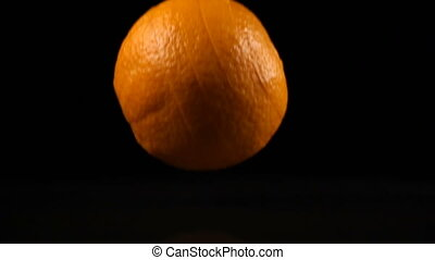 orange slices fall on the black surface covered with water,...