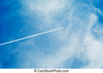 vapor trail from a passenger plane in the blue sky with...