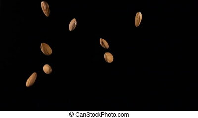 almonds in free fall on a black background