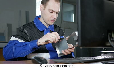 Male engineer measures the item and enter the data into a...