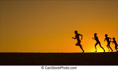 silhouette of five running kids against sunset