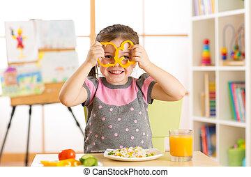 child girl eating vegan food having fun in kindergarten -...