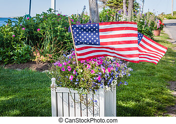 Flags fly with patriotic potted flowers