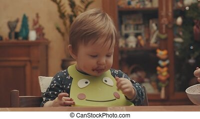 Somebody feeds the baby with a spoon, then she takes food from the bowl by hand