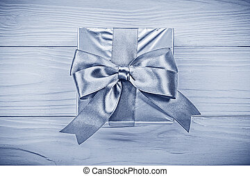 Present box on wooden board directly above holidays concept.