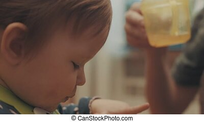 Somebody giving the baby drink from a cup. Close up