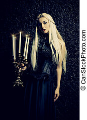 Beautiful gothic lady in long black dress standing with...