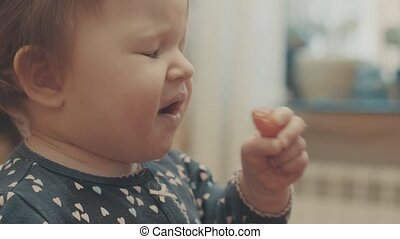 Little baby eating tomato, then puckering of sour. Close up