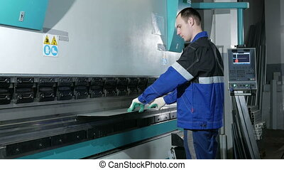 Man working with sheet metal on CNC hydraulic press brake....