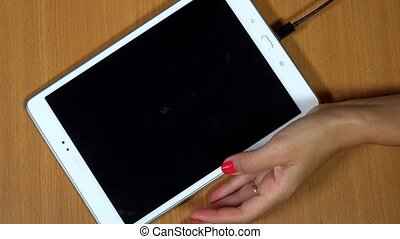Female hangs plug micro USB wires into white tablet...