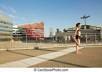 Portrait of a young woman stretching leg muscles outdoors