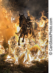 A man riding his horse jumping throug the fire - Men rides...