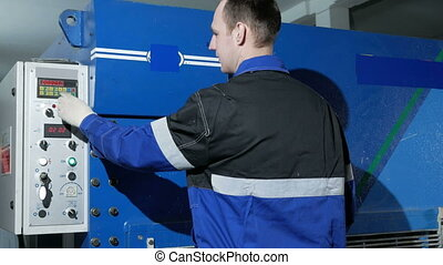 Man adjusts operation of the machine for cutting sheet metal on a large hydraulic guillotine shears. Ironing presses the button and starts the production of parts