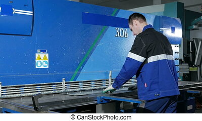 Man cutting sheet metal in large hydraulic guillotine...