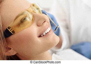 Happy patient treating oral cavity in dental room