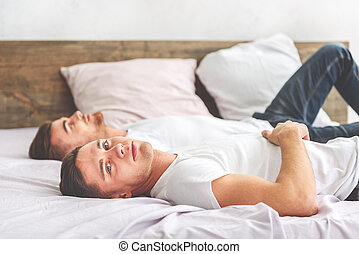 Serene homosexual couple lying in bedroom - Calm young gays...