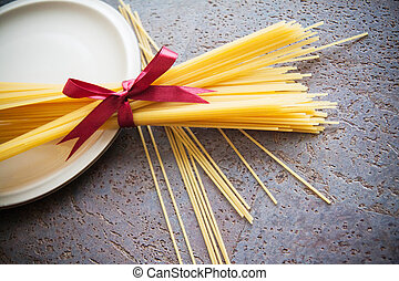 raw italian noodles spaghetti on table in kitchen - raw...