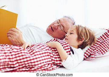 grandpa reading a book to his ill grandchild in bed