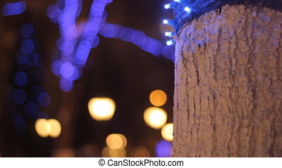 Christmas and New Year background. Abstract blurred bokeh. Blinking garland on a tree.